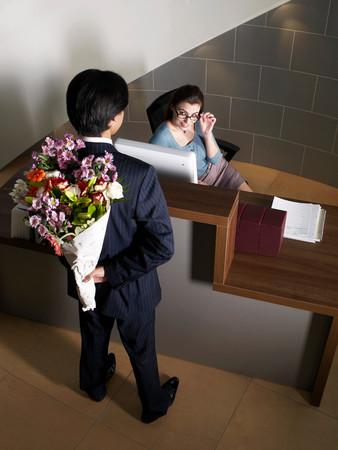 Office Receptionist With Male Worker Foto de archivo