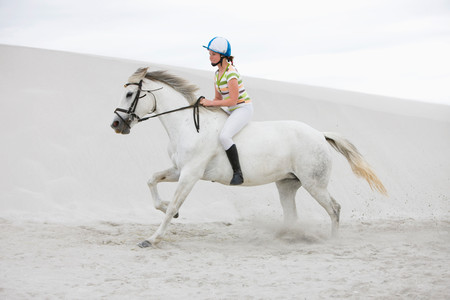 Young Girl Riding Horse On The Beach