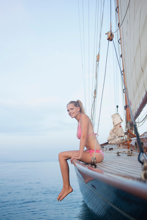 Woman Sitting On Rail Of Sailing Boat