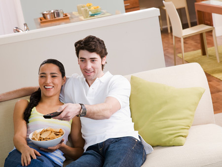 Couple Sitting On Couch Watching Tv Banque d'images - 117922967