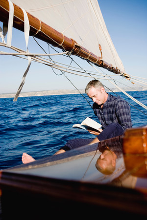 Man Reading Sitting On A Sailing Boat