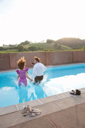 Couple Jumping Into Pool, Dressed Imagens
