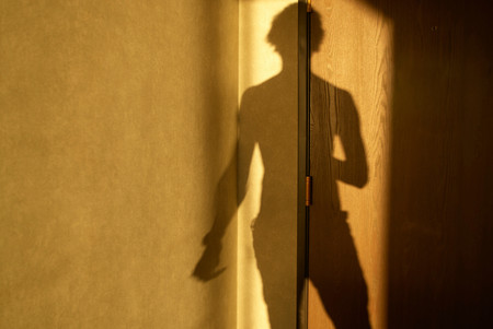 Shadow Of Man On Hotel Room Door Stock Photo