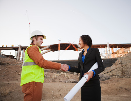Man And Woman On Work Site Shaking Hands