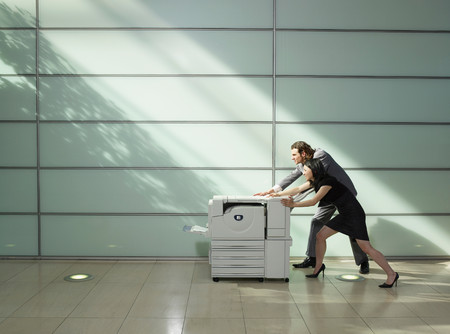 Man And Woman Pushing A Copier 스톡 콘텐츠 - 117923844