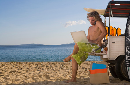 Man At Beach Jeep With Laptop, Phone Imagens