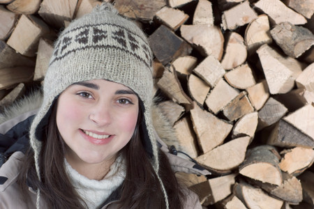Young Woman In Front Of Wood Smiling Stock Photo