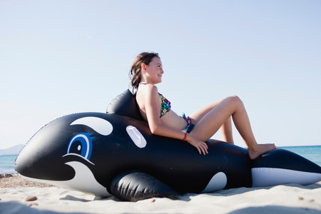 Young Girl Sitting On Toy Whale