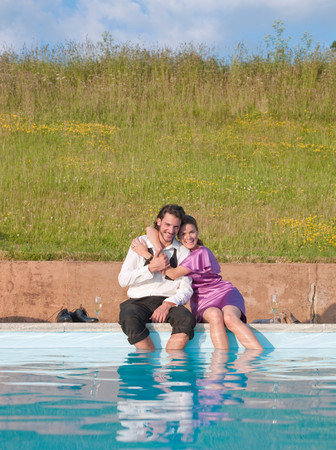 Couple Sat By Swimming Pool, Embraced Imagens