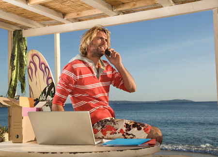 Surf Man On Phone And Laptop At Beach 免版税图像