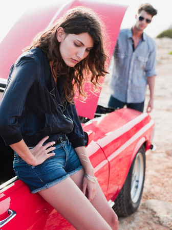 Couple Standing At Car With Opened Hood
