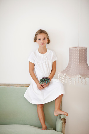 Girl With Flowers Standing On Couch Standard-Bild