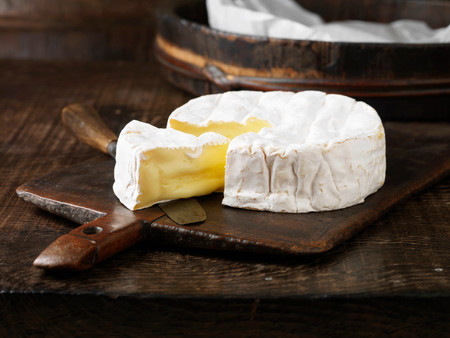 Sliced Camembert Cheese On Board Stockfoto