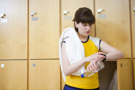 Woman Checking Watch In Locker Room