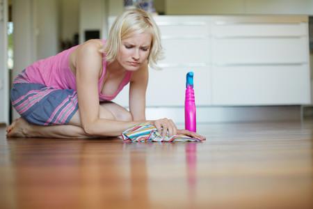 Frowning Woman Polishing Wooden Floor