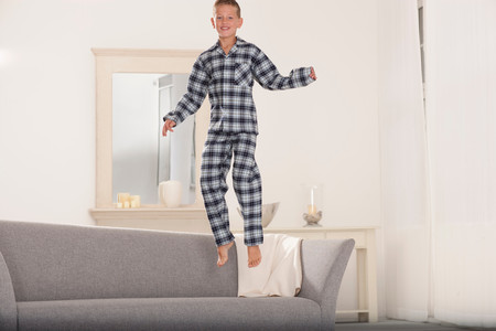 Boy In Pajamas Jumping On Couch