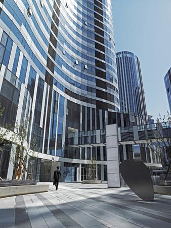 Businessman In Courtyard Of Skyscraper