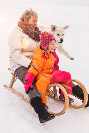 Grandmother And Granddaughter On Toboggan In Snow