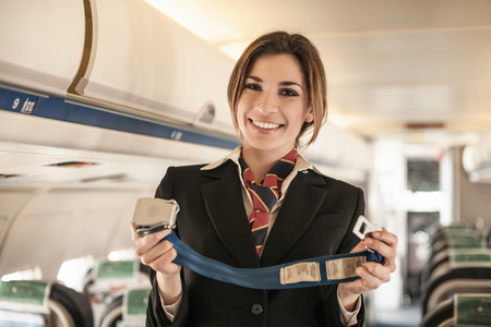 Air Stewardess Performing Safety Demonstration On Aeroplane