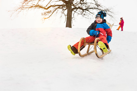 Boy On Toboggan In Snow