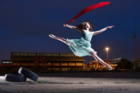 Young Female Dancer Leaping In Urban Environment