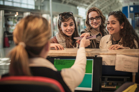 Woman And Two Teenage Girls At Airport Check In Area