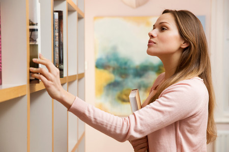 Young Woman Choosing Book From Bookcase Stock fotó