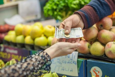 Shopkeeper Handing Change To Female Customer In Market