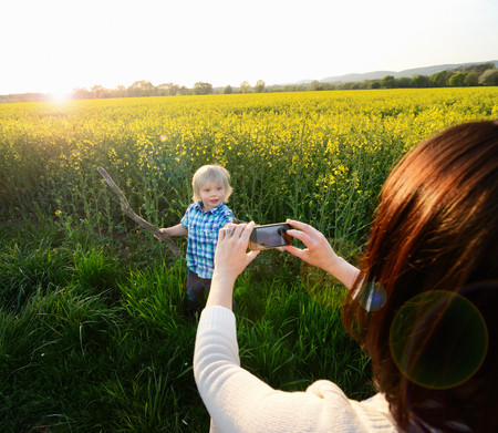 Mother Photographing Son On Smartphone In Field 스톡 콘텐츠