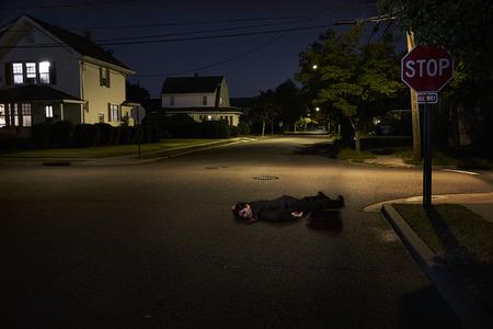 Businessman Lying On Suburban Street Unconscious At Night