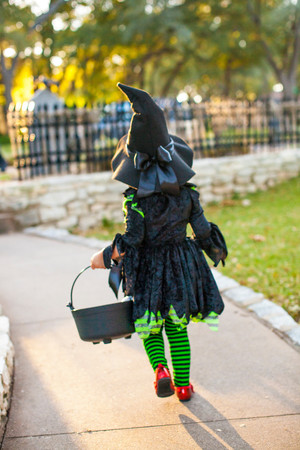 Back View Of Child In Witch Costume With Bucket Of Treats