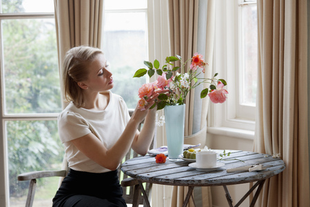 Woman Arranging Roses In Vase Stock Photo