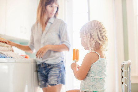 Girl Holding Ice Lolly, Mother In Background Stock Photo