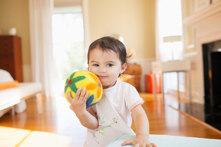 Smiling Baby Girl Pressing Yellow Floral Ball Against Cheek