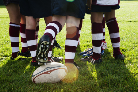 Teenage Schoolboy Rugby Team Kicking Ball From Huddle