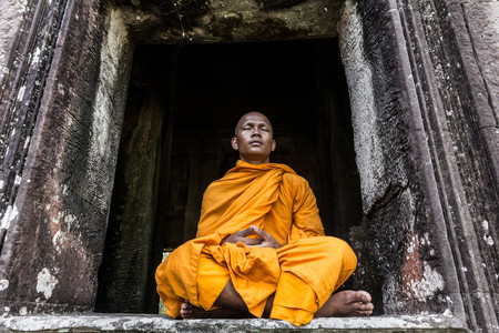 Young Buddhist Monk Meditating In Temple In Angkor Wat, Siem Reap, Cambodia Stock Photo