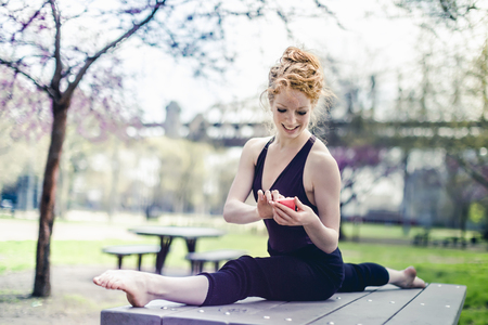 Modern Dancer Striking A Pose And Using A Smart Phone In A Urban Park
