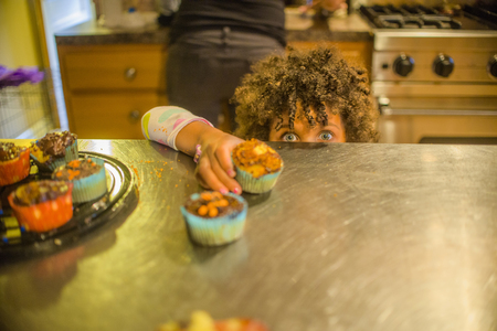 Portrait Of Girl Reaching For Cupcakes At Kitchen Counter