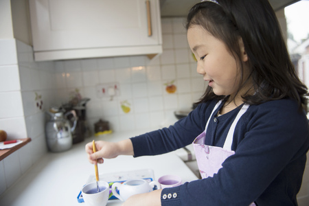 Young Girl Dipping Paintbrush In Water Bowl In Kitchen Фото со стока