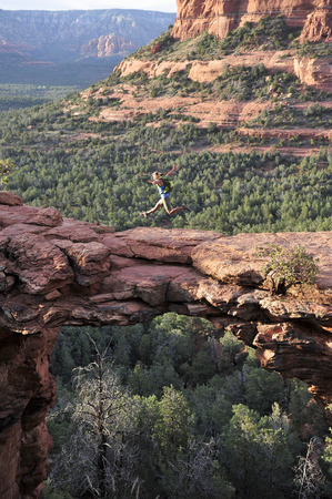 Female Hiker Jumping Mid Air On Arched Rock Formation, Sedona, Arizona, Usa