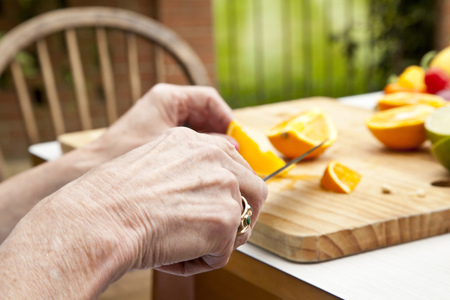 Hands Of Senior Woman Slicing Oranges At Garden Table