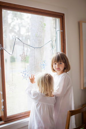 Children Admiring Ornamental Snowflakes On Glass Window 스톡 콘텐츠