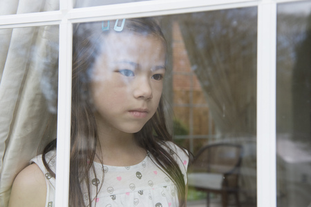 Unhappy Young Girl Looking Out From Sitting Room Window