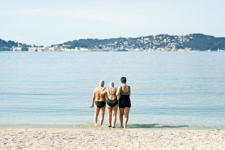 Three Senior Friends Walking Into The Sea, Rear View