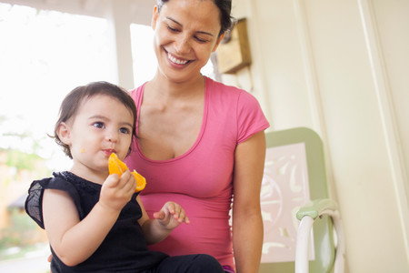 Mother Looking At Baby Girl Eating Slice Of Orange