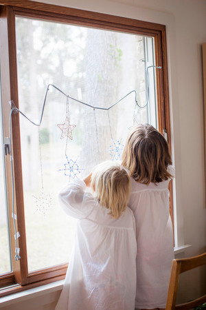 Children Admiring Ornamental Snowflakes On Glass Window 스톡 콘텐츠
