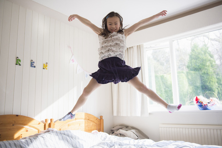 Young Girl Jumping Mid Air On Bed