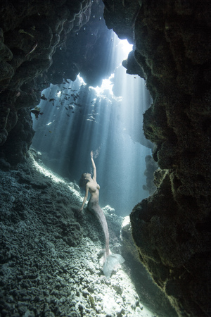 Underwater View Of Mermaid Looking Up From Sea Cave Stock Photo
