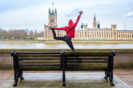 Young Male Dancer Mid Air In Front Of Parliament, London, Uk
