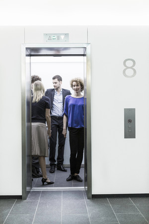 Businesspeople Standing In Lift 版權商用圖片